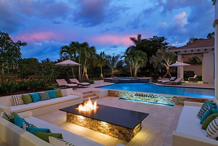 Night time view of a pool with sunken seating and firepit at an Estate lot in Estuary - Naples, Florida