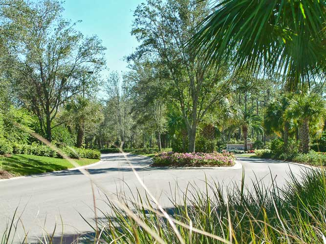 A divided roadway with landscape median in Mediterra - Naples, Florida